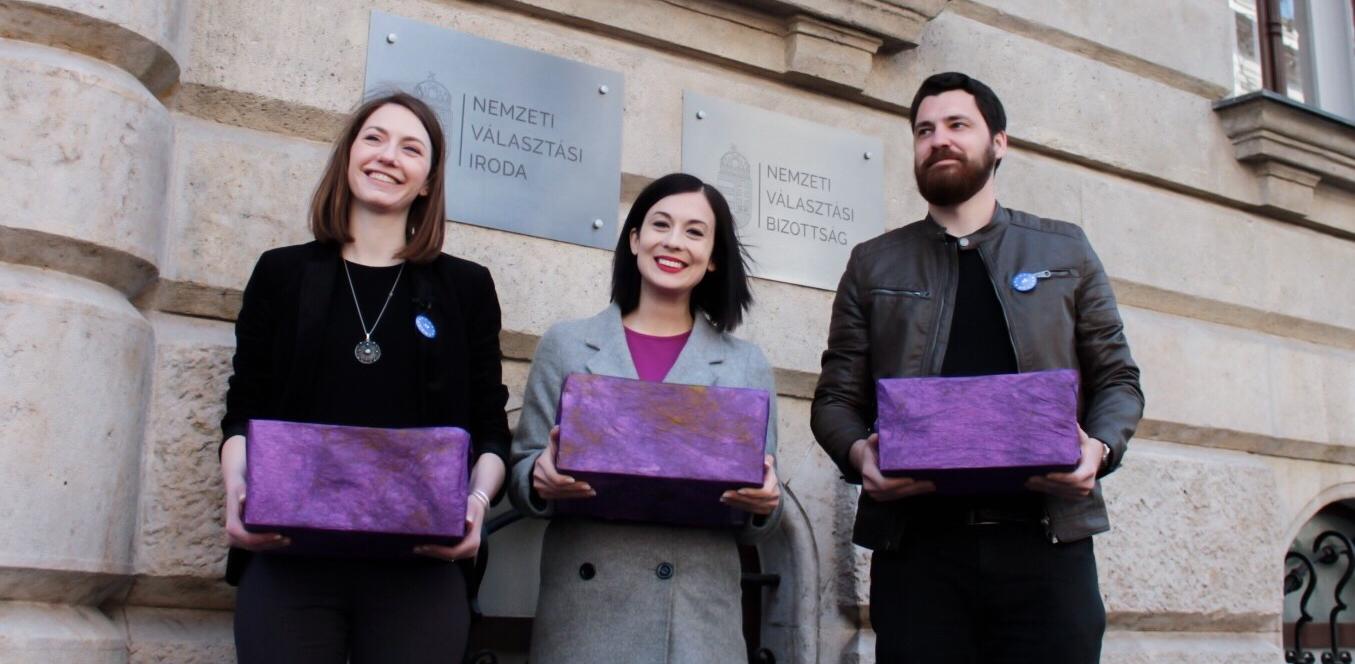 Donáth Anna, Cseh Katalin és Nemes Balázs lila dobozokat tartanak